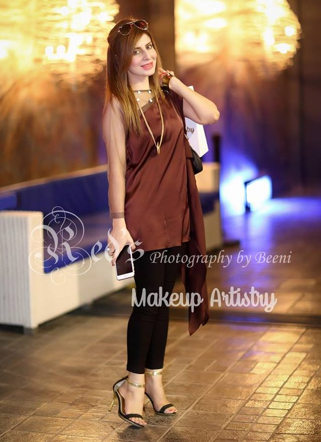 brown tunic paired with black tights and golden pendant