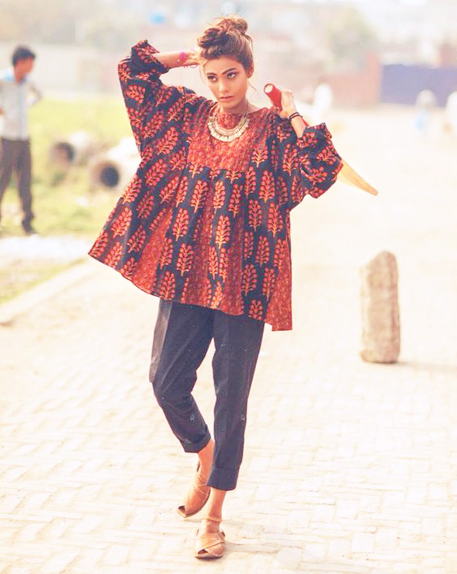 orange printed kurta with plates paired with black tights
